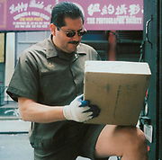 UPS postal worker signing a delivery on a box USA