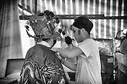 Helping out with last minute adjustments backstage at the Chinese opera. The dressing room is a simple tent with makeshift preparation areas. The I-Hsin opera troupe are preparing for a performance.