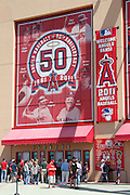 ANAHEIM - APRIL 10:  Fans cue up to the ticket window below a sign featuring the Los Angeles Angels of Anaheim 50 year anniversary logo and players on the exterior wall of the stadium prior to the game between the Toronto Blue Jays and the Los Angeles Angels of Anaheim at Angel Stadium in Anaheim, California on Sunday April 10, 2011. The Angels won the game 3-1. (Photo by Paul Spinelli/MLB Photos via Getty Images)