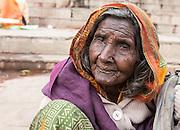 Alte Frau am Ufer des Ganges. Wie viele alte Leute ist sie vermutlich hierher gekommen, um von diesem heiligen Ort ins Jenseits zu gehen wenn ihre Zeit gekommen ist. Hier, früh am Morgen haben ihr Anwohner warmen Tschai Tee und Brot zum Frühstück gebracht.