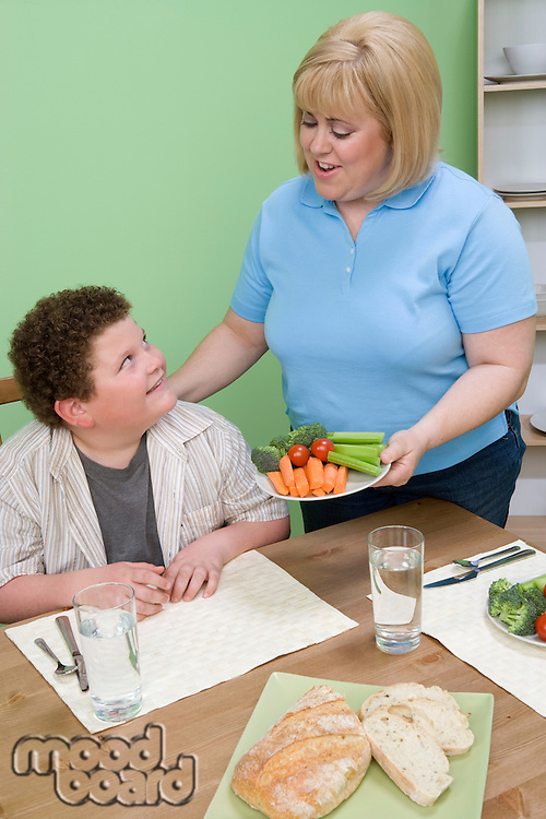Mother serving her overweight son healthy meal