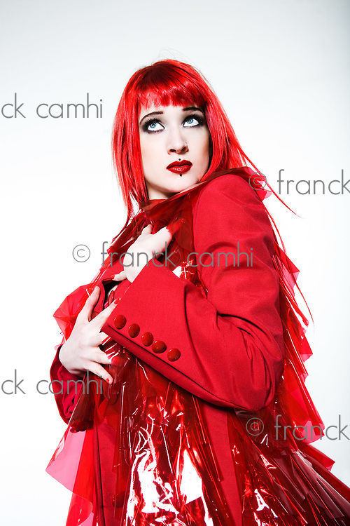 Funny & sexy expressive redhead girl wearing a palstic coat and dress on isolated background