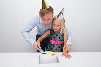 Father and daughter cutting birthday cake at table