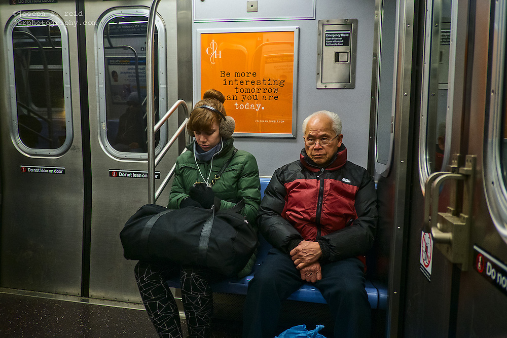 """Subway riders and advertisement reading """"Be more interesting tomorrow than you are today"""", New York, NY, US"""