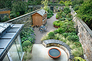 Aerial view over the garden showing the polished sandstone patio, lily bowl, curved scorched oak bench seat and raised borders
