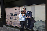 A Londoner walks past a closed shop poster featuring a businessman wearing a blue suit - a favoured style and colour of menswear in the City of London, the capital's financial district - aka the Square Mile, on 29th August 2018, in London, England.