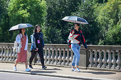 © Licensed to London News Pictures. 01/08/2018. LONDON, UK.  Tourists shelter from the heat of the sun under umbrellas during warm weather in Hyde Park.  Temperatures are forecast to increase back to the 30s in time for the weekend  Photo credit: Stephen Chung/LNP