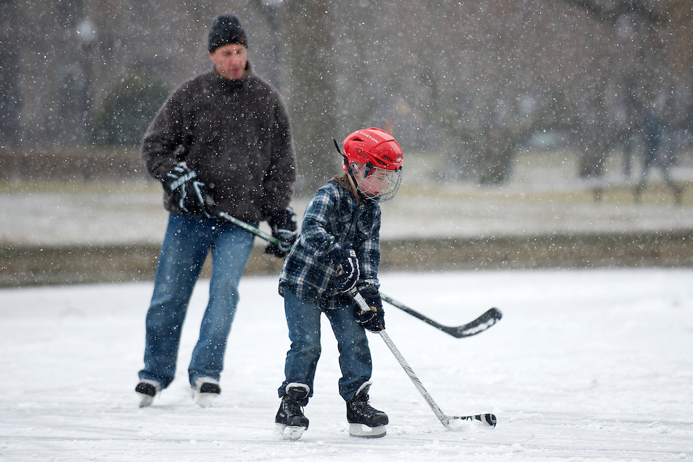(20130208, Boston, Massachusetts)-..Liam Flaherty, 7, skates with his dad, Joe, on the Duck Pond in the Boston Common as snow falls during the beginning of Winter Storm Nemo in Boston, Massachusetts on Friday, Feb. 8, 2013...Photo by Brooks Canaday/The Weather Channel