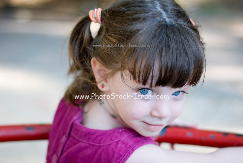 young girl of 3 in a playground, facing camera Model Release available