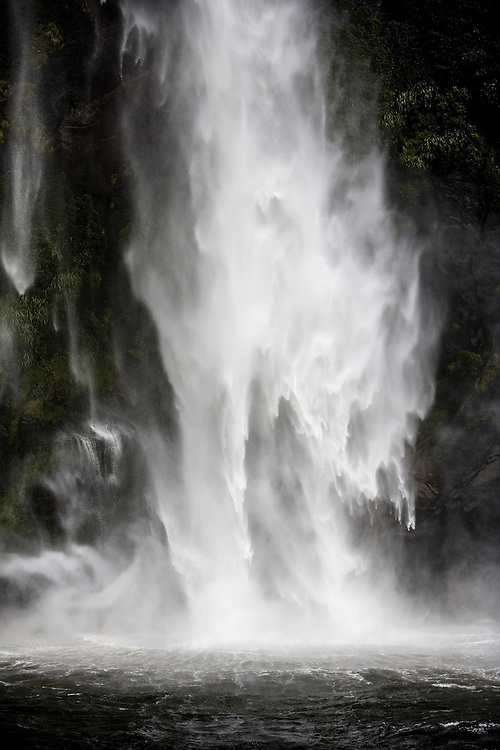 Gushing waterfall cascades into Milford Sound from beech forest in Fiordland National Park in New Zealand.