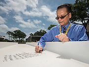 Jonathan Trinh signs a beam during a ceremony at Lee High School, May 25, 2016.