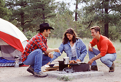 three friends enjoying a cook out at a campsite
