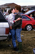 Kiss 3. Part of a series of images produced by the photographer while travelling  as a working photo-journalist on the subject of 'love'.<br /> A couple embrace at the Grand National in 1985