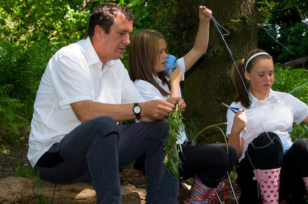 Children being shown how to make dream catchers in the Forest School in Garscaden Woods, Glasgow, Scotland