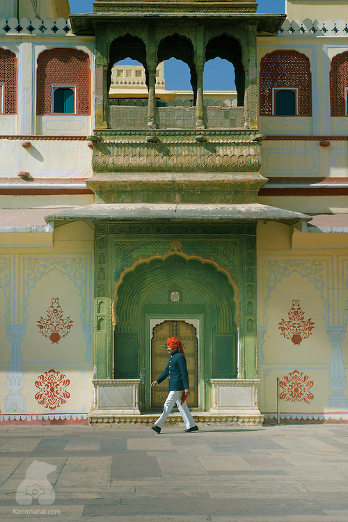 "A man wearing a red turban walks in the Pritam Niwas Chowk courtyard located inside the ""City Palace"" in Jaipur, Rajasthan, India. The vast palatial complex, also known as ""Chandra Mahal"", was built by Maharaja Sawai Jai Singh II -  the founder of the city of Jaipur - in the middle of the 18th century. The palace is one of the major touristic attractions of Jaipur."