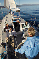 Man Piloting Sailboat While Friends Relax