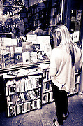 Young woman reading at Shakespeare and Company bookstore, Left Bank, Paris, France