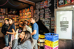 © Licensed to London News Pictures. 27/09/2015. City, UK. Customers in the Cereal Killer cafe in Brick Lane, unaware of the paint attack during the previous night by activists protesting against gentrification in London's East End. Photo credit : Stephen Chung/LNP