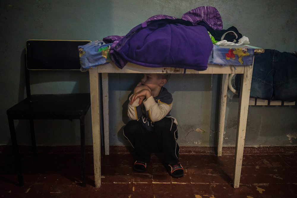 A boy plays hide-and-seek at Romashka, a summer camp where he and several hundred other people live after being displaced by fighting in Eastern Ukraine on Friday, February 13, 2015 in Kharkiv, Ukraine.
