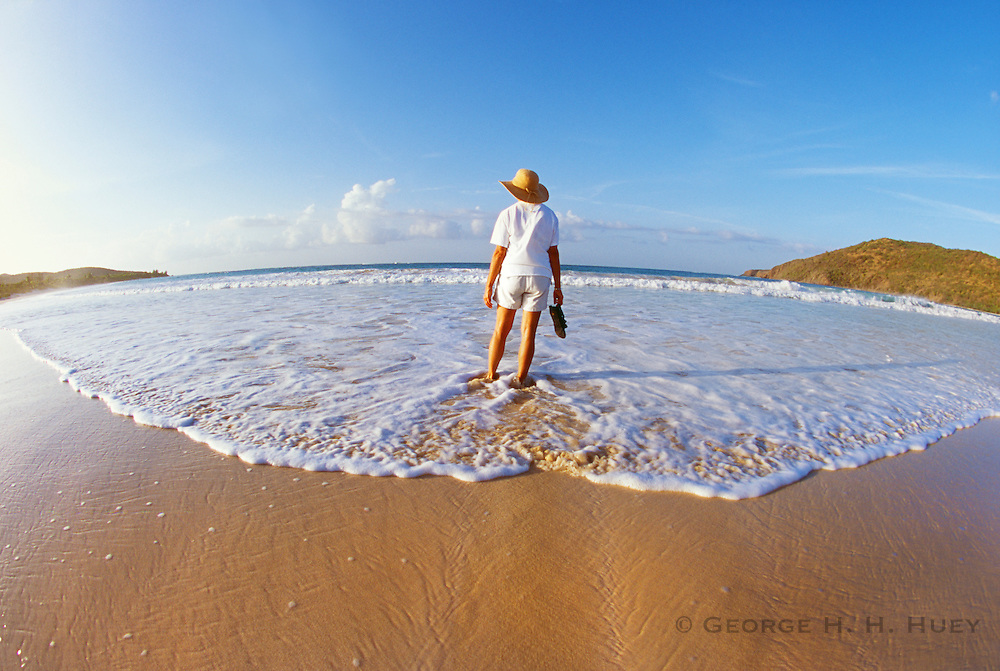 356205-101 ~ Copyright: George H.H. Huey ~  Tourist wading in the surf at Flamenco Beach on Isla Culebra, off the east coast of Puerto Rico. Model release #130.