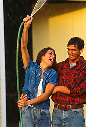woman spraying water into the air from a garden hose on a man