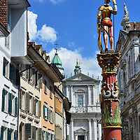 Saint Ursus Fountain and Cathedral in Solothurn, Switzerland <br /> Ursus is the patron saint of Solothurn, Switzerland.  He was a Roman Christian who was beheaded in 286 AD for refusing to worship false gods, along with Saint Victor and 66 other soldiers who had converted to Christianity together.  This fountain in Marktplatz, which was created in 1545 by Albrecht von N&uuml;rnberg, shows the saint in his Theban Legion uniform.  In the background is the Cathedral of St. Ursus where he is buried.