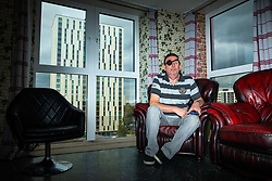 © Licensed to London News Pictures . 11/10/2018. Salford , UK . Thorn Court resident JON SMITH (72) in his flat with a view of Spruce Court through his living room window . Recently installed cladding at several council-owned tower blocks in Salford has been identified as having similar dangerous properties to that which was installed on the Grenfell Tower in London . Residents have been waiting months for clarification on what action will be taken to make their homes safe . Photo credit : Joel Goodman/LNP
