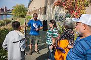 Hunts Point, Bronx, New York - Rocking the Boat director Adam Green explains the recuritment process to local resident Jodry Rodriguez in Hunts Point, the Bronx, New York on Saturday, October 5, 2013.