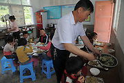 QIANNAN, CHINA - MAY 31: (CHINA OUT) <br /> <br /> Six-pupil School In Mountain Of Qiannan<br /> <br /> The only teacher Wu Guoxian gives out food to students at Gugang primary school in a mountain in Longli County on May 31, 2016 in Qiannan Buyei and Miao Autonomous Prefecture, Guizhou Province of China. Gugang primary school with only one teacher and six students was located in the mountain where the traffic was blocked in Qiannan. 50-year-old Wu Guoxian had been teaching in this school for 33 years and taught over 1,000 students. More and more people went out of the village to work in the cities leaving their children and the old in the mountain. Five under-school-age kids whose parents left for work also stayed at the school. <br /> ©Exclusivepix Media