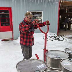 Stainless steel barrels are used to store and transport maple syrup at the LaRiviere family syrup operation in Big Six Township, Maine. Pierre LaRiviere can be seen moving barrels from the sugar house to the driveway for transport to a bottling facility in Madison, Maine.