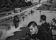 Pont de R&eacute;gina, barrage militaire permanent, Guyane, 2015. <br /> <br /> Eldorado europ&eacute;en enclav&eacute; en Amazonie, la Guyane, avec son niveau de vie &eacute;lev&eacute;, son syst&egrave;me de couverture sociale et ses ressources naturelles, suscite l&rsquo;int&eacute;r&ecirc;t des populations voisines. Dans un premier temps, la construction du centre spatial de Kourou a attir&eacute; une importante main d&rsquo;&oelig;uvre clandestine et depuis le d&eacute;but des ann&eacute;es 2000, l&rsquo;envol du cours de l&rsquo;or entraine un afflux massif de garimpeiros ill&eacute;gaux depuis le Suriname ou le Br&eacute;sil. <br /> <br /> Le gouvernement fran&ccedil;ais tente de r&eacute;agir &agrave; cette perte de souverainet&eacute; nationale sur le territoire guyanais. Depuis 2002, les services de la police, des douanes, de la gendarmerie et de la l&eacute;gion sont associ&eacute;s dans des op&eacute;rations coordonn&eacute;es ; 350 militaires et 200 gendarmes sont aujourd&rsquo;hui d&eacute;ploy&eacute;s sur les r&eacute;seaux fluviaux ou en for&ecirc;t pour d&eacute;manteler les sites d&rsquo;orpaillage ill&eacute;gaux. <br /> <br /> Depuis 2000, le pr&eacute;fet de Guyane prend une succession d&rsquo;arr&ecirc;t&eacute;s d&eacute;cr&eacute;tant l&rsquo;&eacute;tablissement de postes fixes de gendarmerie aux fins de contr&ocirc;les de police administrative. La prorogation r&eacute;p&eacute;t&eacute;e de l&rsquo;arr&ecirc;t&eacute; institue la mise en place de barrages permanents et permet des contr&ocirc;les d&rsquo;identit&eacute; syst&eacute;matiques. <br /> <br /> Depuis mars 2013, le barrage militaire permanent de B&eacute;lizon a &eacute;t&eacute; d&eacute;plac&eacute; sur le pont de R&eacute;gina, proche de la fronti&egrave;re br&eacute;silienne. Un second barrage est en fonction &agrave; Iracoubo, dans l&rsquo;Ouest guyanais &agrave; proximit&eacute; de la fronti&egrave;re Surinamaise. <br /> <br /> Les passeurs s&rsquo;adaptent &agrave; cette n