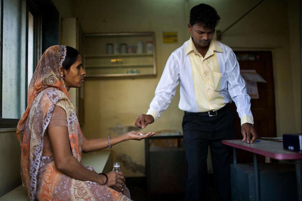 Mangesh Salvi, a health worker at the Thakkar Bappa DOTS Center, gives medicine to Sumitra Bora.