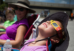August 21, 2017 - St. Pete Beach, Florida, U.S. - VICTORIA REPACZKI-JONES, 5, checks out the sun towards the beginning of the solar eclipse along with her mom, RAMONA (center) and older brother XAVIER, 9, from St. Petersburg, while camped out in the parking lot of the St. Pete Beach Public Library. The Library hosts a Beach Chair Eclipse Viewing from 1 pm - 4:30 pm and provided free eclipse glasses. (Credit Image: © Dirk Shadd/Tampa Bay Times via ZUMA Wire)