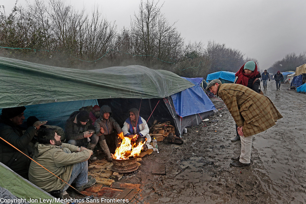 Refugees huddle around a fire to keep warm in heavy rain and freezing temperatures in the refugee camp in Grande Synthe, Dunkirk: <br />