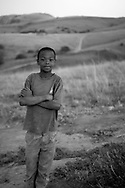 A young boy pictured at dusk near his home, a farm in the Drakensberg mountains, north of Mbabane, Swaziland. The Kingdom of Swaziland (population 1.1m), a small, landlocked country in southern Africa was bordered by South Africa on three sides and Mozambique to the east, with Mbabane as its administrative capital. At the start of the 21st century, the country had the highest incidence per head of population of HIV/Aids in the world and and high levels of poverty mainly in rural areas where 75 per cent of the population lived.
