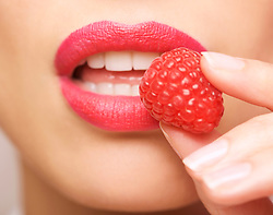 Extreme close up of a woman's lips eating a raspberry