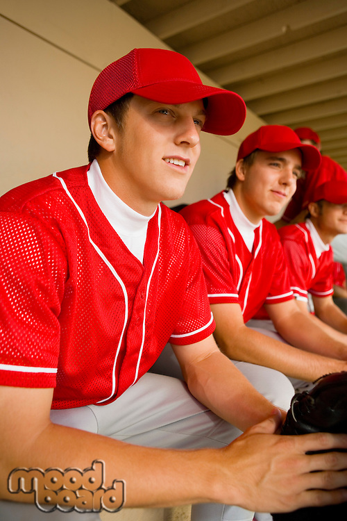 Baseball team-mates sitting in dugout