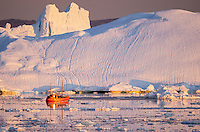 Red tourist boat in the glacial ice during the last light near Illussat, Greenland.