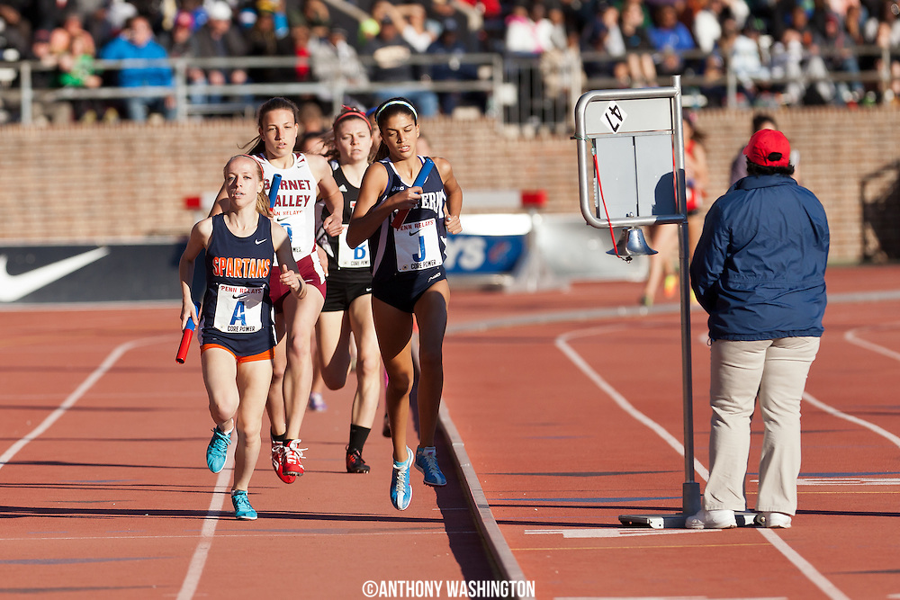 Caroline Alcorta of West Springfield High School (left) takes the lead in the High School Girls' Distance Medley Championship of America before crossing the finish line first at the Penn Relays on Thursday, April 24, 2014 in Philadelphia, PA.