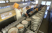 Chris Renard carrries large wheels of cheddar cheese to a cooler as Paul Stockwell, middle, and Don Stockwell pull the compressed cheese from hoops at Renard's Cheese in southern Door County, WI Monday morning May 12, 2003.