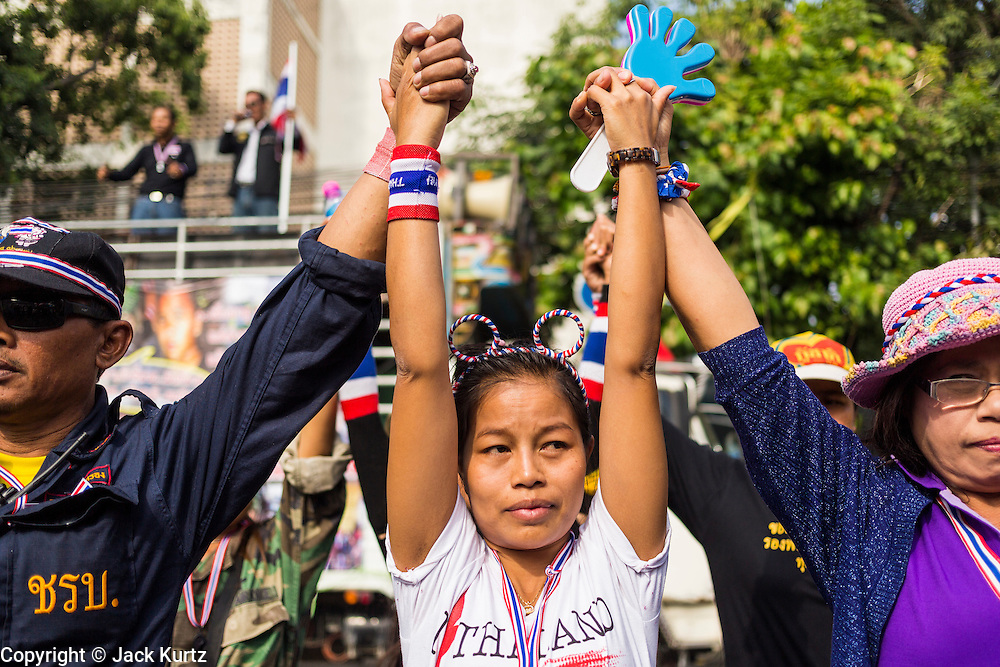 24 DECEMBER 2013 - BANGKOK, THAILAND: Anti-government protestors raise their hands over their heads while they block the gates to the Thai-Japan Stadium in the Din Daeng section of Bangkok. Hundreds of anti-government protestors are camped out around the Thai-Japan Stadium in Bangkok, where political parties are supposed to register for the election on February 2. As of Dec 24, nine of the more than 30 parties were able to register. Protestors hope to prevent the election. The action is a part of the ongoing protests in Bangkok that have caused the dissolution of the elected government.      PHOTO BY JACK KURTZ