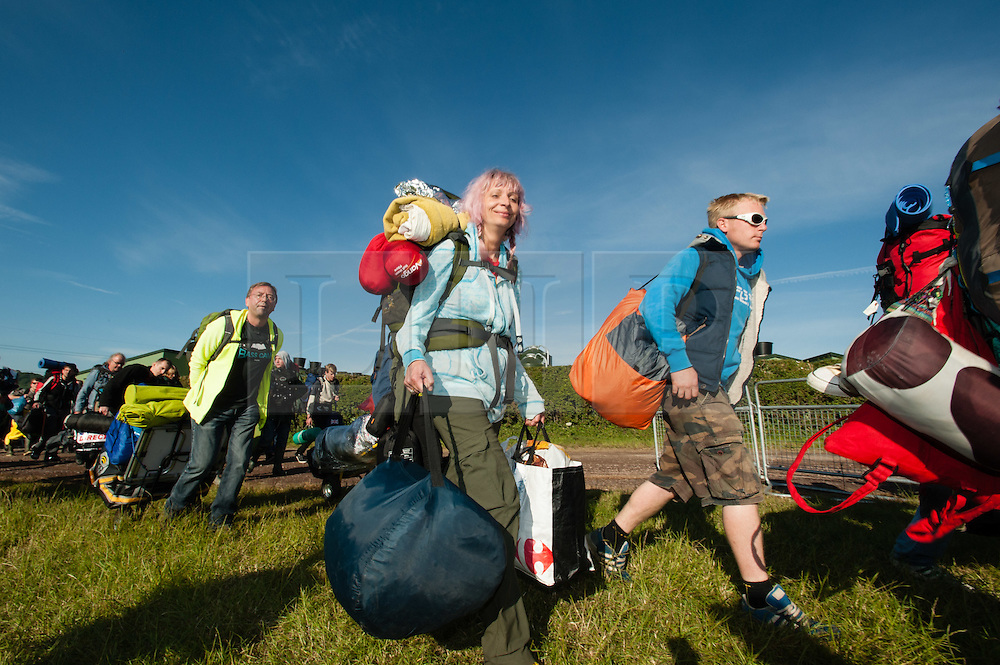 © Licensed to London News Pictures. 24/06/2015. Pilton, UK.   Festival goers stream in through the gates of Glastonbury Festival 2015, at 8am as the gates open of  Wednesday Day 1 of the festival.        The pedestrian gates to the festival opened at 8am this morning, with many festival goers arriving and waiting throughout last night for the opening.  This years headline acts include Kanye West, The Who and Florence and the Machine, the latter having been upgraded in the bill to replace original headline act Foo Fighters.  Photo credit: Richard Isaac/LNP