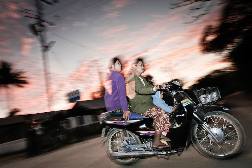 Two women travel with scooter on a village near Lake Inle.