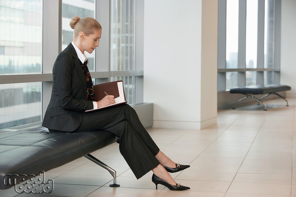 Businesswoman writing in planner in office lobby