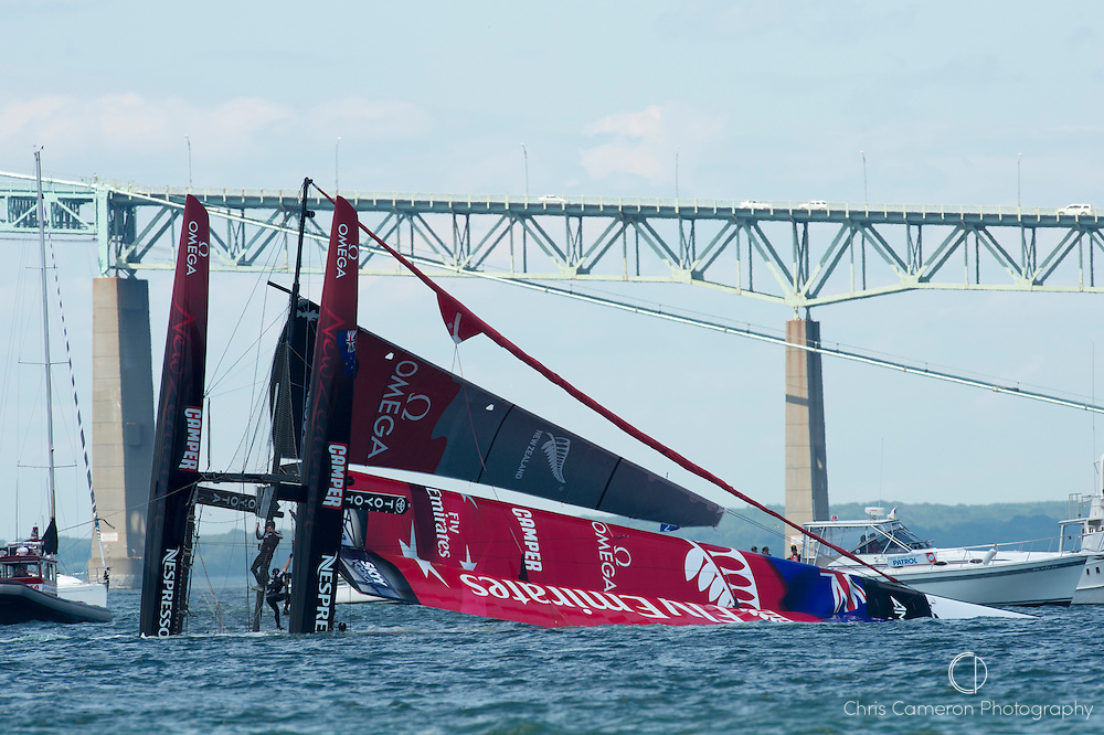 Emirates Team New Zealand  struggles to right their AC45 as the wing tip fills with water. ETNZ capsized at the first top mark in their first match race against Luna Rossa Piranha. America;s Cup World Series Regatta in Newport, Rhode Island, USA. 28/6/2012
