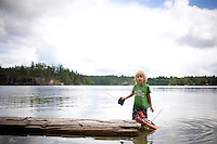 A young boy plays with a remote controlled boat in Hague Lake on Cortes Island in British Columbia, Canada
