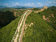 Drone aerial flying over the famous Great Wall defensive barrier designed to prevent invasion from Mongolian invaders. Today it is one of the most famous vacation destinations on the UNESCO word heritage list.
