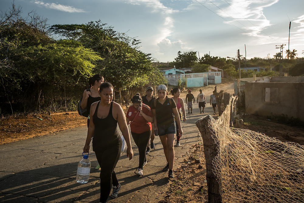FALCÓN, VENEZUELA - SEPTEMBER 26, 2016: Undocumented migrants walk to the beach to board the smuggler's boat that will illegally take them from Venezuela to Curaçao. Undocumented migrants here have mortgaged property, sold kitchen appliances and even borrowed money from the same smuggling rings that pack them on the floorboards alongside drugs and other contraband. The journey to Curaçao takes them on a 60-mile crossing filled with backbreaking swells, gangs of armed boatmen and coast guard vessels looking to capture migrants and send them home. Then, after being tossed overboard and left to swim ashore, they hide in the brush to meet contacts who spirit them anew into the tourist economy of this Caribbean island. They clean the floors of restaurants, work in construction, sell trinkets on the street, or even solicit Dutch tourists for sex. But at least, the migrants say, there is food. PHOTO: Meridith Kohut for The New York Times