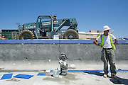 Enes Vukovic of Bosnia waits for another construction worker while laying down lane marker tiles in the warming pool at Milpitas High School in Milpitas, California, on July 18, 2014. (Stan Olszewski/SOSKIphoto)