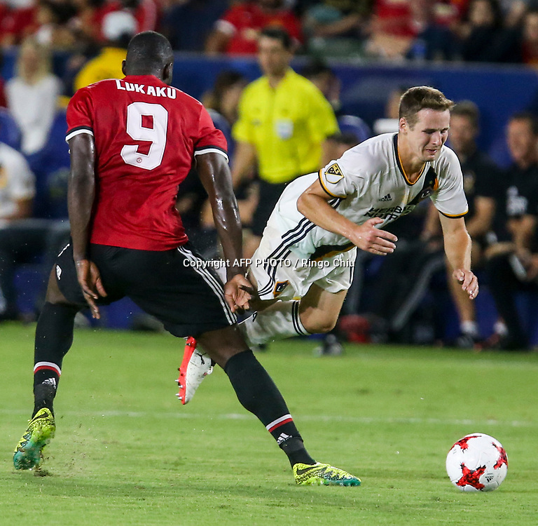 Los Angeles Galaxy Nathan Smith, right, crashes with Manchester United Romelu Lukaku during the second half of a national friendly soccer game at StubHub Center on July 15, 2017 in Carson, California. Manchester United won 5-2. AFP PHOTO / Ringo Chiu